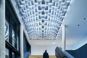 """Über der Sitztreppe im Foyer schebt eine 5,5x8m große Licht-skulptur, die sogenannte """"Cloud"""", die das Aushängeschild für den Leuchtenhersteller darstellt. Sie besteht aus einzelnen Leuchtkacheln"""