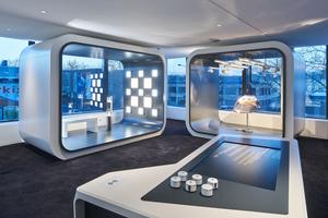Auf der Galerie im zweigeschossigen Foyer stehen Ausstellungskuben, in denen die Produkte des Bauherrn präsentiert werden