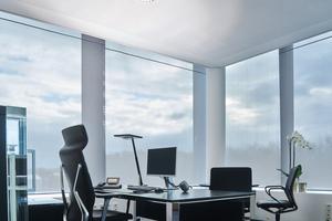 In der weißen, perforierten Abhangdecke über den Arbeitsplätzen gibt es keine Leuchten – stattdessen individuelle Tischleuchten
