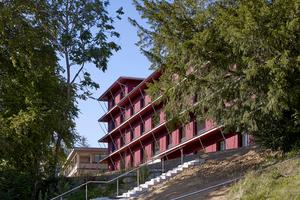 Ein charakteristischer Holzbau mit ortstypischen geschosshohen konstruktiven Holzschutzelementen, die das Gebäude horizontal strukturieren und die roten lasierten Schalungen entsprechend schützen.