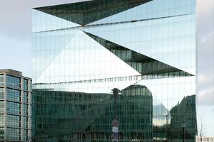 In der gefalteten äußeren Glashülle spiegeln sich Himmel und Betonfassaden