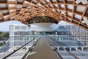 Die organische geformte Gitterschaltenkonstruktion überbrückt den Hayek-Platz und dockt auf dem Dach des Museumsneubaus Cité du Temps an