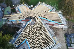 Das realisierte Stabnetztragwerk der Dachschale besteht aus 762 verschiedenen Holzbalken. Es liegt einerseits auf den Seitenwänden auf, andererseits auf den gebogenen Stahlbetonbalken über den raumhohen Fensterfronten mit den Festverglasungen