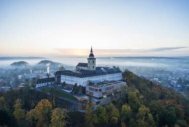 Ein Ort des Glaubens sensibel in die Zukunft geführt: die denkmalgeschützte Abtei Michaelsberg ragt imposant über Siegburg. Ab 2014 wurde sie umgebaut