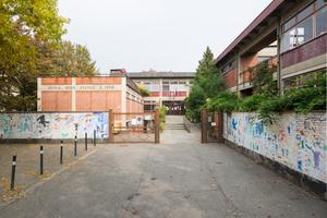 Die Enrico Fermi Schule war ursprünglich ein Bau aus den 1960er Jahren. Das Bild zeigt den ehemaligen Haupteingang zur Schule