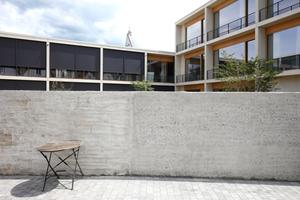 Die zwei- bis dreigeschossige Bürobebauung zeigt sich von der Spitalmauer aus gesehen zeitgenössisch. Oben die Giebelspitze der entkernten Kapelle
