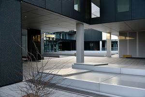 """Auch unterhalb des großen Gebäudevolumens können Passanten ihren Weg finden und das Spiel mit verschiedenen Ebenen und Fassadengestaltungen wahrnehmen. Die Streckmetallelemente, hier als Fassade zu sehen, wurden in vielen Räumen in Form von <irspacing style=""""letter-spacing: -0.01em;"""">abgehängten Decken ins Gebäudeinnere </irspacing>durchgezogen. Hinter den Streckmetall-elementen befinden sich die Ausstellungsräume"""
