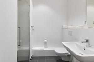 Um den Bau beider Objekte zu beschleunigen und zudem kostensicherer zu gestalten, wurden die Badezimmer mit TECEsystem-Sanitärwänden realisiert. Der Einsatz dieser individuell geplanten und industriell vorgefertigten Segmente half dabei, den Bau planungssicher abzuwickeln. Risiken wie Baumängel oder Verzug konnten dadurch minimiert und Qualität und Kosten optimiert werden. Zudem kamen auch das Fußbodenheizungssystem TECEfloor sowie abdichtungssichere Entwässerungstechnik von TECE zum Einsatz