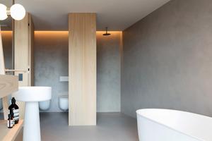 Von Hand verspachtelte Kunstharzböden ziehen sich ohne Materialwechsel durch die Gästezimmer bis zur Loggia.