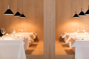 Von der Terrasse geht der Blick ins Restaurant, das klar gegliedert und zurückhaltend in der Materialität gestaltet ist