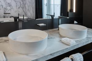 Wirkungsvoller Kontrast: die schwarzen Armaturen und Accessoires auf weißem Marmor-Waschtisch. Die IXMO Armaturen in der Dusche zeichnen sich durch die Bündelung von Funktionen aus. In der Oberfläche Schwarzchrom gebürstet, setzen sie, genauso wie die flache Kopfbrause, ein edles Design-Statement. Dazu passend: die Accessoires rund um das WC mit PVD-Oberfläche von KEUCO