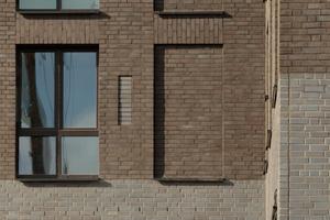 Der Sockel beider Bauteile glänzt anthrazitfarben, während die Vormauersteine des Schafts erdig warm erscheinen. Die runden Fenster signalisieren den Eingang und spielen mit dem Formenvokabular des Hafentypischen