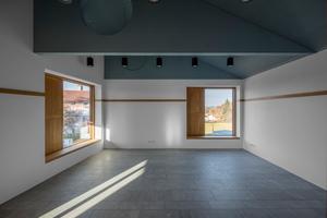 Der grünblaue Farbton des Dachstuhls wurde von der Balustrade des Baudenkmals entlehnt und schafft so eine visuelle Verbindung zum Kontext. Dass damit auch noch die Assoziation des Himmels über Bayern verbunden wird, macht das Konzept wieder rund