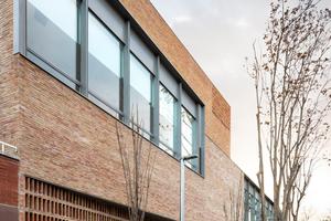 Das Filtermauerwerk an der Straßenfassade gibt Einblicke in das Innere des öffentlichen Gebäudes frei