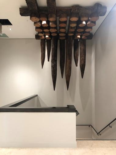 """Abgang in den """"Schlosskeller"""": Feng Shui technisch gesehen eher ein Wagnis, unter den wie Damokles-Schwertern drohenden Eichenpfählen der historischen Schlossgründung die Treppe hinabzusteigen"""