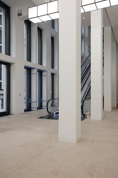 """Eingang und Verteilzentrum vom Schlossforum aus. Von hier geht es direkt über die Rolltreppe in die Dauerausstellung, oder man nimmt die stehende Treppe gegenüber. Oder man läuft geradeaus weiter und gelangt in den """"Agora"""" genannten, haushohen Empfang"""