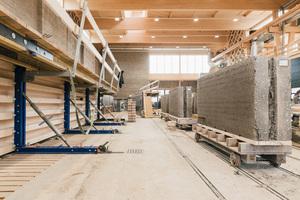 Die Halle ist Hybrid einer Holzkonstruktion die von der 67m langen Stampflehmwand getragen wird