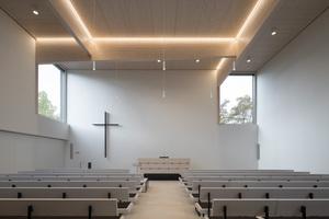 Im Inneren der Neuapostolischen Kirche Böblingen ist es a+r Architekten gelungen, mit weiß lasiertem Holz, weiß verputzten Wände sowie einem sandfarbenem Sichtestrich Helligkeit und Leichtigkeit in die Räume einziehen zu lassen. In dieser maßvollen Inszenierung bekommt auch der Umgang mit der Beleuchtung eine tragende Rolle