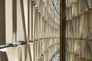 Die Keramikbaguettes von MOEDING sorgen für Lichtspiele im Gebäudeinneren und erscheinen außen wie eine abstrakte Bücherfassade. Realisiert wurde diese mithilfe der insgesamt 7714 länglichen Keramikbaguettes in der Größe 120x60cm. Zur Befestigung dienen spezielle Tragprofile auf einer systemspezifisch, gebogenen Stahlunterkonstruktion, die eine schnelle und einfache Montage und einen späteren Austausch ermöglichen. Ein Kriterium für die Wahl der Keramikbaguettes war neben eines recyclebaren Fassadensystems auch der Anspruch der ArchitektInnen, einen möglichst nachhaltigen und langlebigen Baustoff zu verwenden