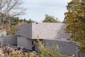 Der Baustoff Holz sollte so umfangreich wie möglich eingesetzt werden. So orientiert sich auch die Fassaden mit ihrer Holzschindel-Verkleidung an der umgebenden Natur