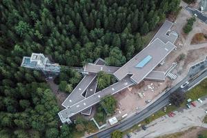 Das Nationalparkzentrum im Schwarzwald entstand am teilweise steil abfallenden Gelände. Die weit auskragenden, übereinander gestapelten Riegel sind in Hybridbauweise gebaut, um die enormen Lasten optimal zu bewältigen. Vorgefertigte Elemente wurden auf der Baustelle zusammengefügt