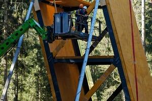 Konstruktion des 34m hohen, um 15Grad geneigten Aussichtsturms: Er steht am tiefsten Punkt des Besucherzentrums und ist über den Skywalk erreichbar. Die Konstruktion aus Brettsperrholz und Stahl ist am Fußpunkt in ein Blockfundament eingespannt. Stahlgurte in Verbindung mit Stahlstreben stabilisieren das Brettsperrholz in den hochbelasteten Anschluss- und Eckbereichen. Horizontale Ebenen aus Brettsperrholz steifen die Konstruktion aus