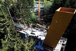 """<irspacing style=""""letter-spacing: -0.01em;"""">Die Tragstruktur entwickelt sich beim Skywalk mit 5m hohen V-Fachwerken als Brückenträger aus Brettschichtholz. Die Träger lagern seitlich am Aussichtsturm auf und verlängern sich zu einer großen, in den Wald auskragenden Balkonstruktur. Parallel zur Turmmontage wurde der erste Teil des Skywalks als Gesamtquerschnitt auf einem Vormontageplatz zusammengebaut und auf Riegel D sowie einem Hilfsturm abgesetzt. Die restlichen Längsfachwerkträger wurden aufgrund ihrer unterschiedlichen Längen und Passungen am Turm einzeln eingebaut, die Quer- und Aussteifungs-Elemente folgten. Abschließend wurden die auskragenden Balkonelemente eingehoben</irspacing>"""