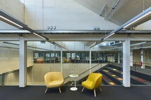 Teppichboden direkt auf der temperierten Decke, Holzaufbauten auf dem Ortbetonsockelgeschoss: hinter den Möbeln die große Treppe als offener Veranstaltungsraum