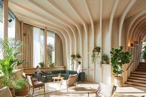 Topfpflanzen säumen die Wände bis zum Zwischengeschoss. Regale, die in die Wände und die Treppe eingelassen sind, bieten den Gästen des Zentrums die Möglichkeit, ihre eigenen Objekte hinzuzufügen, damit sie sich mehr zu Hause fühlen