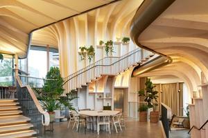 Das Team von Heatherwick Studio entwarf zwei Kork- und Buchenholztische für das Maggie's Center, die die gewölbte Form der tragenden Holzkonstruktion des Neubaus widerspiegeln