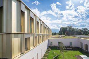 Die Fassade ist modular aufgebaut, tiefe Kastenelemente und Fenster wechseln einander ab. Sie reichen bis zum Boden und sollen die optische Nähe nach draußen zum Grün vermitteln. Ihre Rahmen sind mit goldenem Aluminum eloxiert – ebenfalls eine optische Maßnahme, um das Gebäude für Kinder und Jugendliche möglichst angenhem erscheinen zu lassen