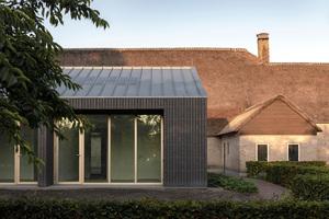 Bronzefarbene Fenster- und Türrahmen sowie ein Zinkdach geben dem schlichten Neubau ein zeitgenössisches Äußeres