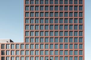 Die gerasterte Fassade aus vorgefertigten Ziegel-/Betonelementen bestimmt das Erscheinungsbild. Viel Wert wurde auf die Ausbildung der Details gelegt