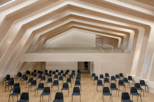 Blick von der Bühne zurück zur Empore in der Aula, die einen Rohbaustand zeigt, der Finish-Qualitäten hat