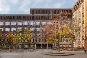 Die Schule, die in Plattenbauweise erstellt ist, haben die ArchitektInnen auf den Dachflächen ein- bis zweigeschossig in die Höhe erweitert. Links im Anschnitt die spektakuläre Dachterrrasse