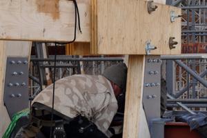"""<irspacing style=""""letter-spacing: 0em;"""">Befestigung der Rahmenträger an der Attika des Bestands. Das horizontale Holz dient der Transportsicherung und wird nach Montage entfernt</irspacing>"""