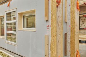 Das Element wird mit einer Holzfaserplatte als wärmebrückenfreie Zusatzdämmung auf der Außenseite verschlossen