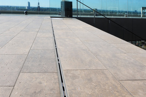 Aufgrund der exponierten Lage der 800m² großen Dachterrasse und des Innenhofs galt es, diese Bereiche bei Niederschlägen effektiv und möglichst unauffällig zu entwässern. Dazu wurde sowohl die Entwässerungsschlitzrinne Lamina aus Edelstahl als auch die Dränagerinne Stabile und die Cubo Rinne von Richard Brink eingesetzt. Die Höhenverstellbarkeit der Schlitzrinnen erleichterte den Ausgleich von Toleranzen, um die Rinnen exakt am Niveau des umliegenden Plattenbelags auszurichten