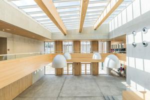 Das zentrale Atrium der Grundschule, das als Versammlungsraum für den gesamten Schulkomplex dient, wird von einem filigranen Glasdach mit vier Reihen Velux Modular Skylights als Stufen-Lichtband-Lösung überspannt. 56 dieser Module wurden eingebaut. Das Glasdach mit integrierter Verschattung und Belüftung wurde innerhalb einer Woche installiert. Alle Elemente sind mit einem innenliegenden, weißen Rollo versehen. Acht Module können zu Lüftungszwecken geöffnet werden, so dass das Glasdach aktiver Bestandteil des Klimakonzepts des Gebäudes ist