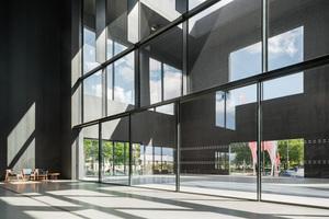 """<irspacing style=""""letter-spacing: -0.01em;"""">In eine gläserne Zwischenfassade des nach oben halboffenen Atriums haben die Architekten zwei großformatige Schiebefenster von Solarlux eingesetzt. Die zwei cero Systeme mit vier und sechs Glaselementen öffnen die Fassade über 18 und 12 m in der Breite und 3,60m in der Höhe und verbinden den Innenhof schwellenlos mit dem Aufgang zum Großen Saal und dem Foyer. Das System wurde ohne Automatikbetrieb ausgeführt. Dank durchdachter Technik können die je 600 kg schweren Elemente dennoch mühelos und leise bewegt werden. Hochtransparentes Isolierglas SKN 176 schützt vor Sonneneinstrahlung. Die 52 mm dicken Glaselemente sind aus VSG gefertigt und bieten, dreifach verglast, mit einem U<sub>g</sub>-Wert von 0,7 W/m²K beste Wärmedämmung</irspacing>"""
