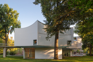 Die Gebäudeform wurde von den umstehenden Bäumen geprägt, die als natürlicher Sonnenschutz dienen. Das weit über das Erdgeschoss auskragende Obergeschoss wird von einer transluzenten Profilglasfassade umhüllt
