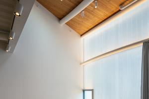 In jedem Atelier wurden in die unteren Ecken der Profilglasfassaden quadratische Fenster eingesetzt, die auch zum Lüften geöffnet werden können. Konstruktiv stellten diese Fenster eine weitere Herausforderung dar: Weil die thermisch vorgespannten Profilgläser nicht tragfähig genug sind, musste für die Fenster ein eigener Stahlrahmen konstruiert werden, dessen Lasten in die Geschossdecken abgeleitet werden