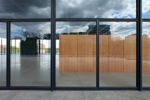 Das neue Glas spiegelt Innen nach Außen und erlaubt weite Durchblicke. Im oberen Fassadenfeld die übergroßen Scheibenformate (3,45x5,40m), made in China