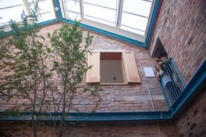 Um für den Bestand eine Lösung zu finden, die die Ruinen erhält, zog Assemble während der Sanierung das Ingenieurbüro Structure Workshop zu Rate. Gemeinsam entwickelte das Team eine Stahlkonstruktion aus zwei hellblau gestrichenen Ringen, die die beiden Häuser bzw. deren Fassaden nun umspannen und so die Bestandswände sichern. Das Glasdach verwandelt die beiden Gebäude in einen großen Wintergarten