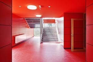 Einfachheit mit Farbstärke: Die vertikale Erschließung sind verzinkte Metalltreppen, die man eher im Außenbereich erwartet