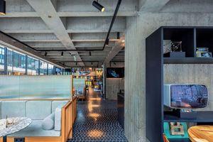 Blick in Lobby und Restaurant im EG unter dem offenen Betontragwerk