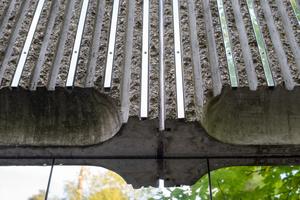 Die kannelierte, raue Fassade haben die Architekten mit schmalen U-Profilen aus dem gleichen spiegelnden Verbundmaterial kunstvoll ergänzt.