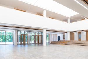 Die eingeschossige, mit einer drückenden Kassettendecke versehene Aula wurde durch einen Teilabbruch des ersten Obergeschosses erweitert und wirkt nun sehr großzügig, beleuchtet durch eine vollflächige Lichtdecke