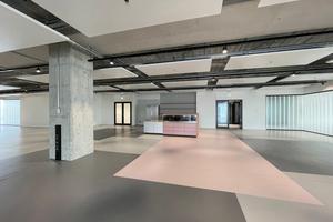 Großzügige Flächen prägen die Büroetagen. Das Farbkonzept stammt von studio aisslinger. Lichtlinien und abgehängte Deckensegel zonieren die ansonsten roh belassenen Decken<br />
