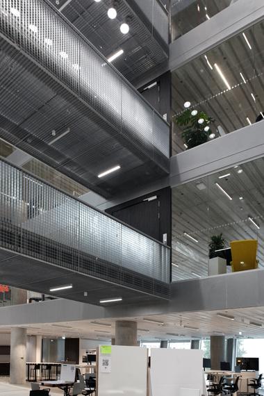 Die transparent geschlossenen Büroebenen werden über offene Brücken an weitere, eben offene Arbeitsflächen angeschlossen